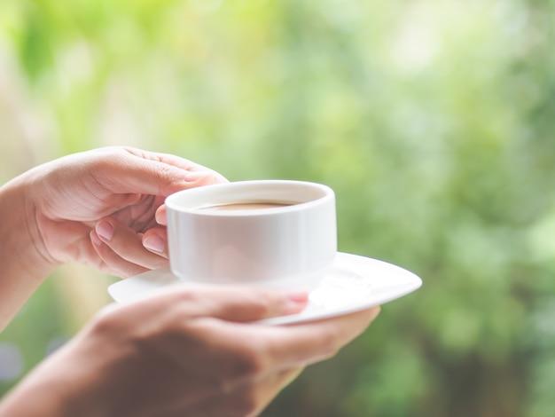 Mano della donna che tiene una tazza di caffè al giardino di mattina