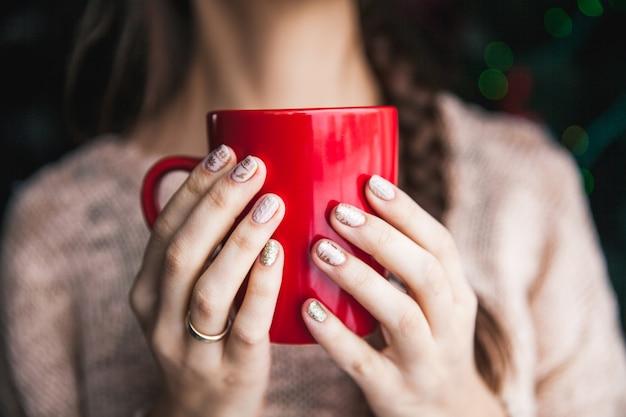 Mano della donna che tiene una tazza di caffè rossa. con una bella manicure invernale. bere, moda, mattina