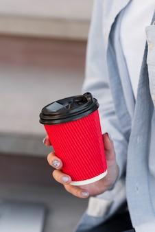 Mano della donna che tiene una tazza di caffè