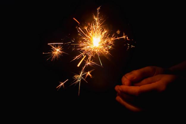 Mano della donna che tiene uno sparkler burning