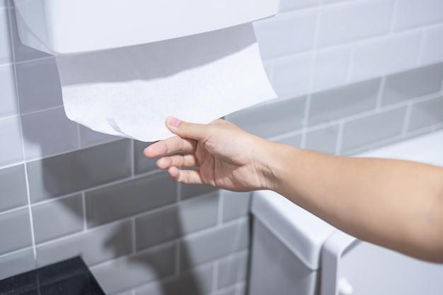 Mano della donna che tira la carta igienica in toilette. pulizia, stile di vita e concetto di igiene personale