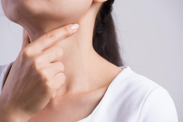 Mano della donna che tocca il suo collo malato