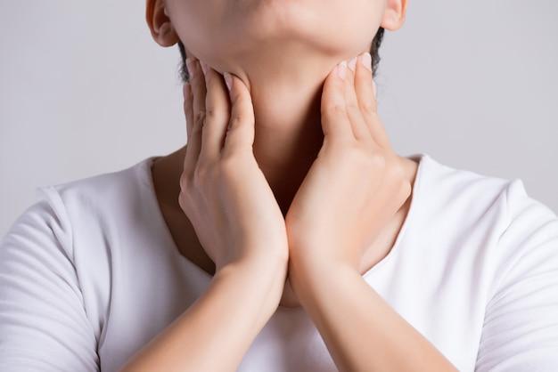 Mano della donna che tocca il suo collo malato.
