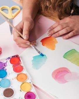 Mano della donna che vernicia progettazione astratta su libro bianco facendo uso dell'acquerello