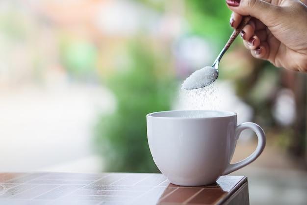 Mano della donna che versa lo zucchero dentro alla tazza di caffè