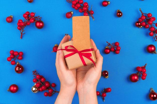 Mano della donna con il regalo sul fondo decorato di natale