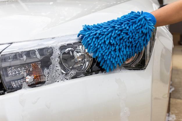 Mano della donna con l'automobile moderna del faro di lavaggio del tessuto blu del microfiber o l'automobile di pulizia.