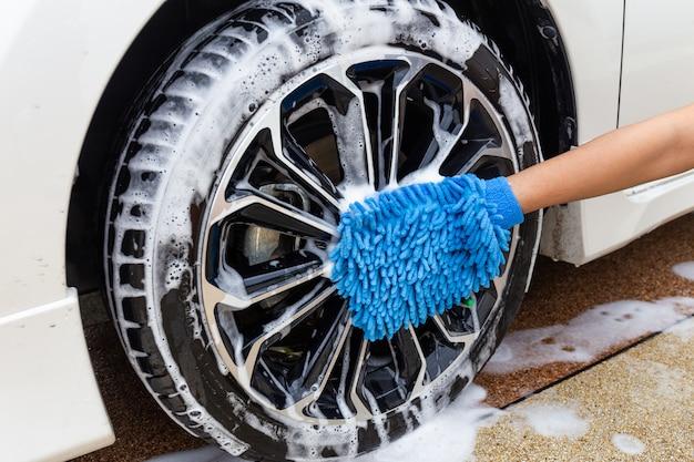 Mano della donna con l'automobile moderna della ruota di lavaggio del tessuto blu del microfiber o l'automobile di pulizia.