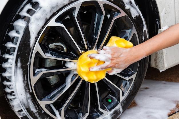 Mano della donna con l'automobile moderna della ruota di lavaggio gialla della spugna o l'automobile di pulizia.