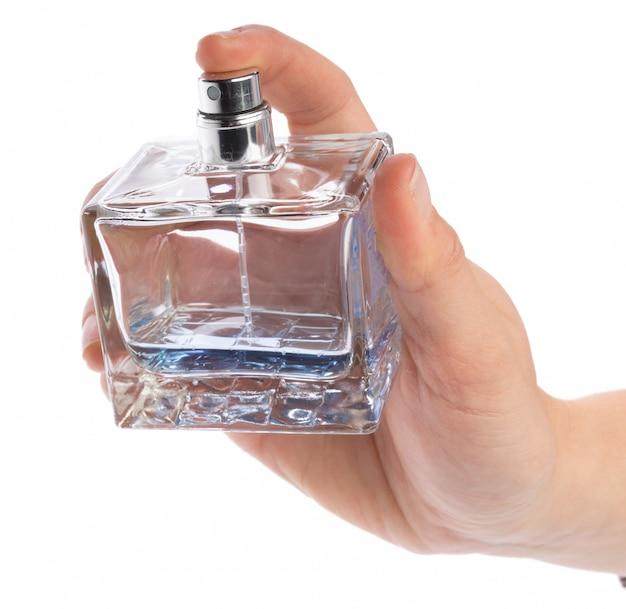 Mano della donna con la bottiglia di profumo isolata su bianco