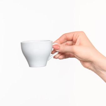 Mano della donna con la tazza su spazio bianco
