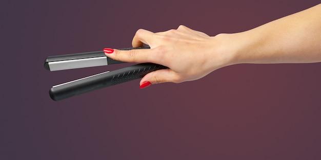 Mano della donna con un ferro dei capelli isolato su una priorità bassa di colore
