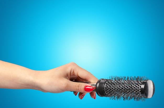 Mano della donna con un pettine dei capelli isolato su un blu
