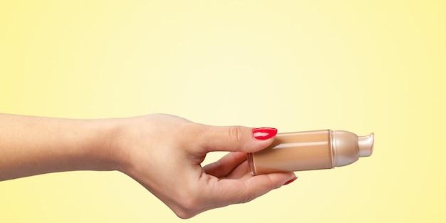 Mano della donna con uno strumento cosmetico del fondamento isolato sul fondo di colore