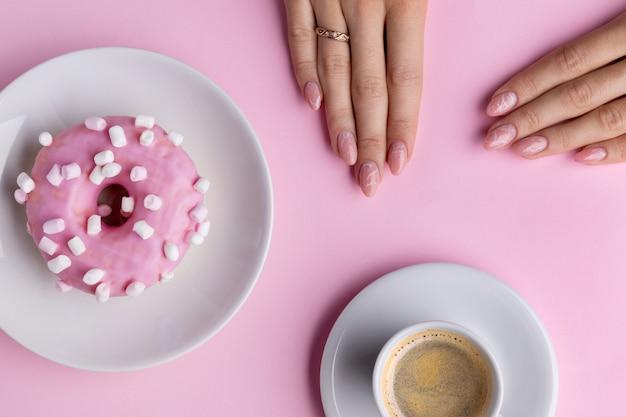 Mano della donna curata con tazza di caffè bianca e ciambella