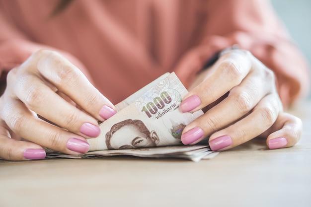 Mano della donna del primo piano che conta soldi tailandesi