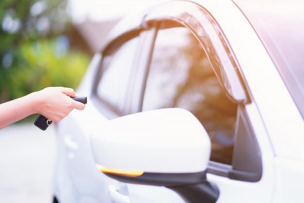 Mano della donna del primo piano che tiene i sistemi di allarme dell'automobile del telecomando