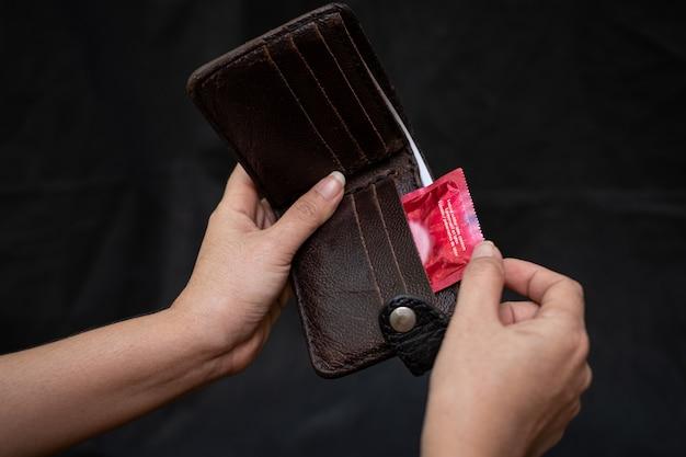 Mano della donna del primo piano che tiene portafoglio di cuoio nero con un preservativo rosso