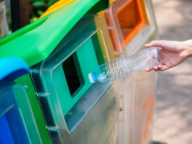 Mano della donna del ritratto del primo piano che getta bottiglia di acqua di plastica vuota nel recipiente di riciclaggio