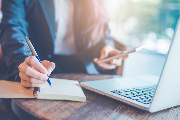 Mano della donna di affari che scrive su un blocco note con una penna e che per mezzo di un telefono cellulare con un lapto