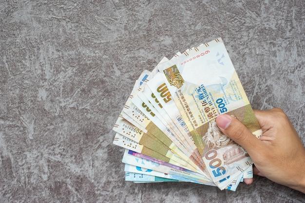 Mano della donna di affari che tiene le banconote di valuta di hong kong, dollari della hk per il fondo di affari