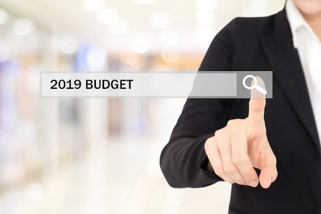 Mano della donna di affari che tocca bilancio 2019 sulla barra di ricerca sopra il fondo dell'ufficio della sfuocatura
