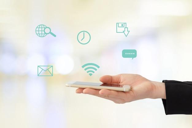 Mano della donna di affari facendo uso dello smart phone con internet dell'icona di cose sul concetto vago del fondo, di affari e di tecnologia