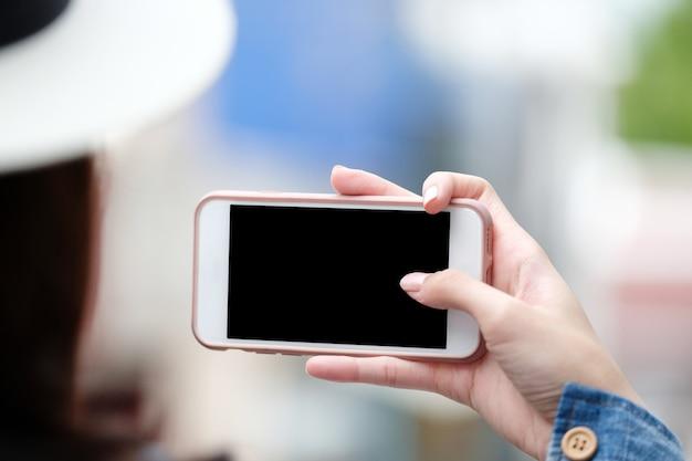 Mano della donna facendo uso dello smart phone con lo schermo in bianco sopra fondo della sfuocatura