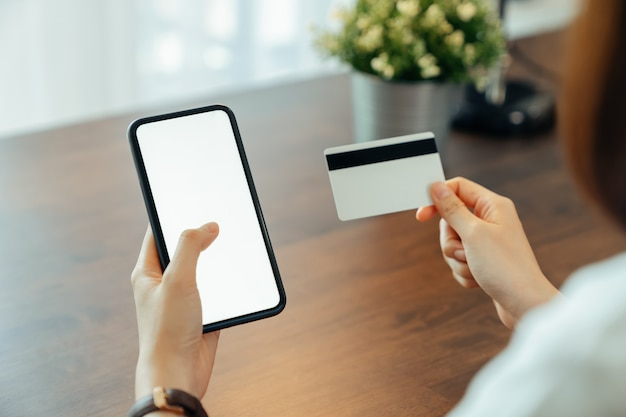 Mano della donna facendo uso dello smartphone e tenendo la carta di credito con il pagamento online sul cellulare.