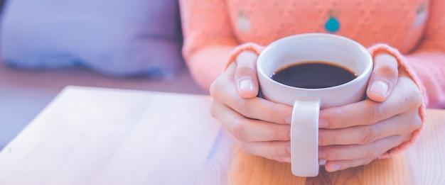 Mano della donna in maglione caldo che tiene una tazza di caffè per l'insegna di web.