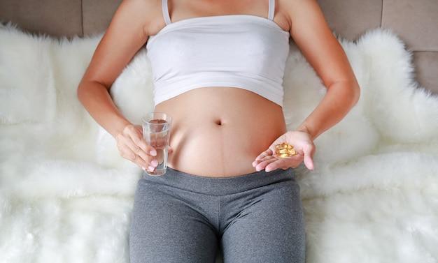 Mano della donna incinta con la pillola della vitamina e del bicchiere d'acqua, donna incinta che prende la medicina a casa.