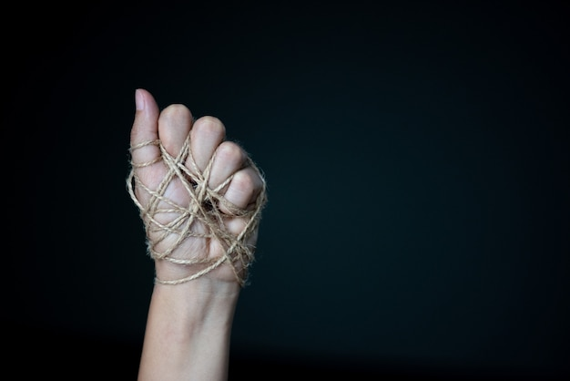 Mano della donna legata con cavo su fondo scuro in concetto scuro di giorno di diritti umani.