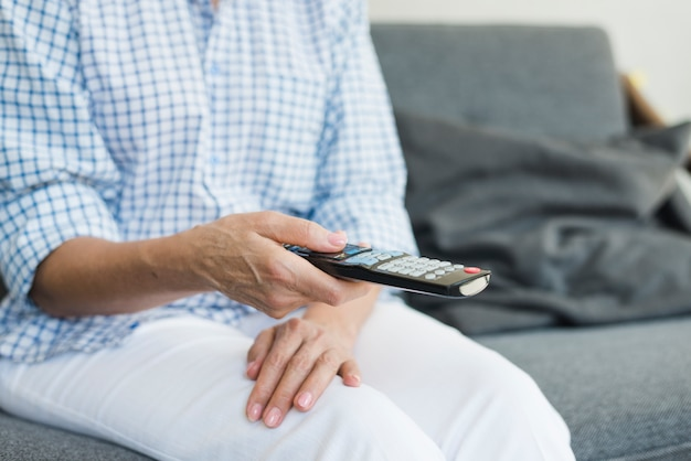 Mano della donna maggiore che tiene telecomando