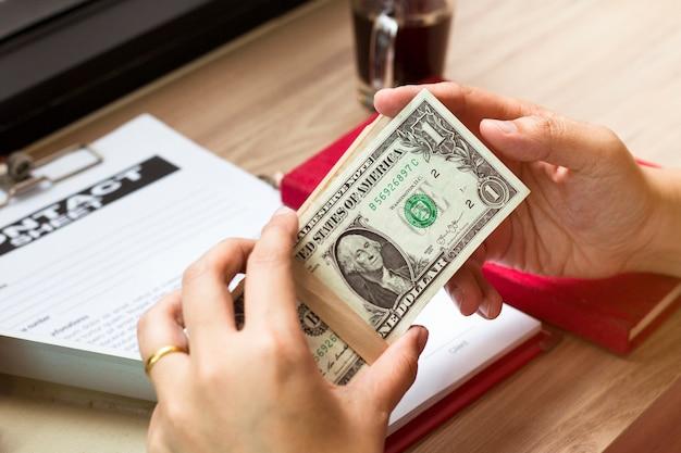 Mano della fattura del dollaro della tenuta dell'uomo d'affari vicino al documento di affari