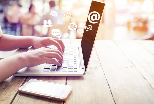 Mano della femmina che per mezzo del computer portatile che invia messaggio di posta elettronica con il simbolo dell'indirizzo email e l'icona della busta. marketing online