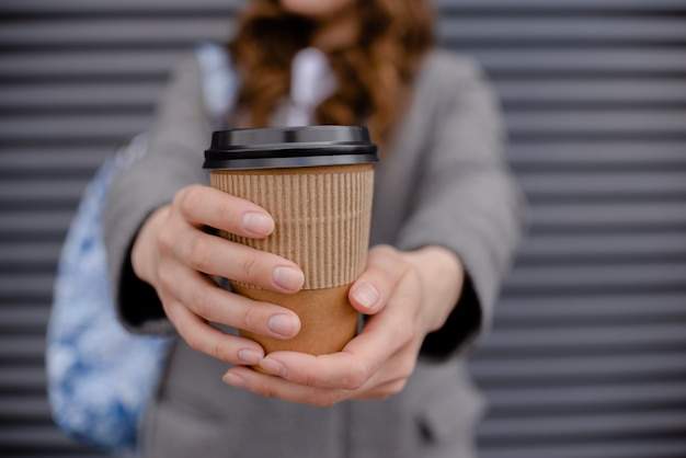 Mano della femmina che tiene tazza da portar via della bevanda calda contro la parete grigia sulla via della città