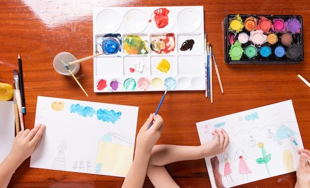 Mano della foto creativa del disegno dei bambini di piccola ragazza dell'asia