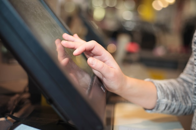Mano della giovane donna che fa pagare un pagamento per alcuni vestiti dal tesoro del touchscreen all'enorme centro commerciale