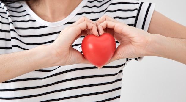 Mano della giovane donna che mostra cuore rosso