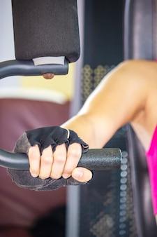 Mano della giovane donna in vestito rosa alla palestra, modello femminile muscolare che si prepara