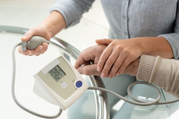 Mano della giovane donna su quella del suo padre malato anziano durante l'assistenza medica e la misurazione della pressione sanguigna