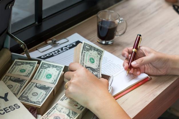 Mano della penna di holding dell'uomo d'affari per scrivere documento di affari e strato del contatto
