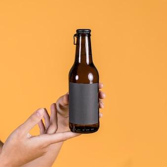 Mano della persona che tiene la bottiglia di birra su sfondo giallo
