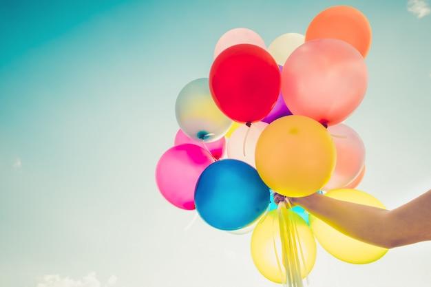 Mano della ragazza che tiene palloncini multicolore