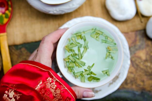 Mano della ragazza che tiene tazza di tè cinese verde sulla metà del giorno di festival autunnale