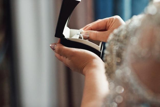 Mano della sposa che tiene bellissimo anello di diamanti