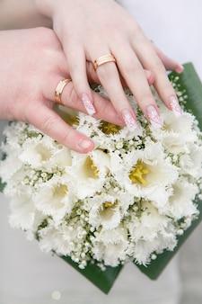 Mano della sposa e dello sposo e anelli sul mazzo di nozze