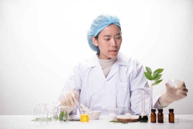 Mano dello scienziato che tiene foglia verde in cuvetta di vetro sul laboratorio. concetto di biotecnologia.