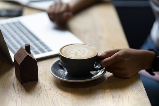 Mano di affari che tiene la tazza di caffè calda e che woking con il computer portatile sulla tavola di legno