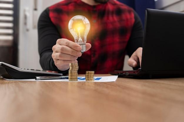 Mano di affari che tiene le lampadine con il computer portatile e soldi impilati nell'ufficio. concetto di risparmio energetico e contabilità finanza nella luce del mattino